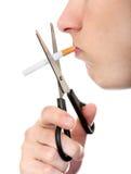 Persona que corta un cigarrillo Fotografía de archivo