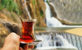 Persona que detiene cierre turco del té negro con el fondo de la cascada imágenes de archivo libres de regalías