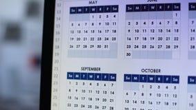 Persona que elige la fecha, mirando a través de calendario en el ordenador, planeamiento de la boda almacen de video