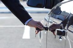 Persona que inserta clave del coche foto de archivo
