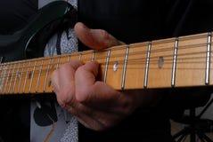 Persona que juega el cuello de la guitarra Imagen de archivo libre de regalías