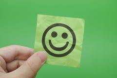 Persona que lleva a cabo la nota del Libro Verde con la cara feliz fotografía de archivo libre de regalías