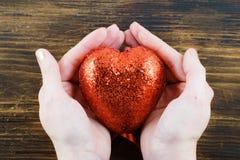 Persona que lleva a cabo un corazón rojo hecho a mano en sus manos Amor El 14 de febrero Día del `s de la tarjeta del día de San  Fotografía de archivo