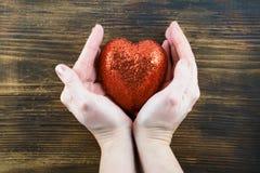 Persona que lleva a cabo un corazón rojo hecho a mano en sus manos Amor El 14 de febrero Día del `s de la tarjeta del día de San  Foto de archivo libre de regalías