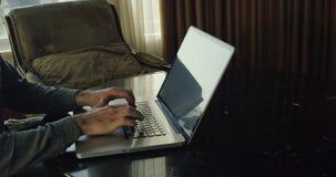 Persona que mecanografía en el teclado del ordenador portátil, freelancer que envía proyecto al cliente por el correo electrónico almacen de video