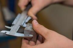 Persona que mide con el pedazo del metal de los calibradores Foto de archivo libre de regalías