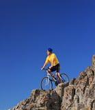 Persona que monta una bici en rocas contra el cielo azul Fotos de archivo libres de regalías
