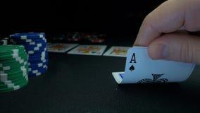 Persona que muestra su cubierta en el juego de póker El jugador de tarjeta llega su mano, dos as, los microprocesadores en fondo  Fotografía de archivo