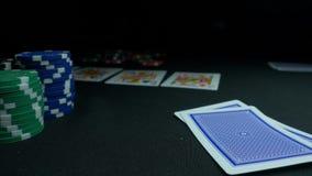 Persona que muestra su cubierta en el juego de póker El jugador de tarjeta llega su mano, dos as, los microprocesadores en fondo  Foto de archivo libre de regalías