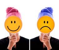 Persona que oculta su cara detrás de smiley felices e infelices Imágenes de archivo libres de regalías