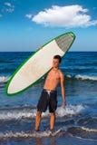 Persona que practica surf adolescente del muchacho que sostiene la tabla hawaiana en la playa Imágenes de archivo libres de regalías