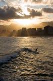 Persona que practica surf bajo puesta del sol Fotos de archivo libres de regalías
