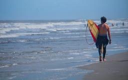 Persona que practica surf que camina abajo de la playa Fotografía de archivo