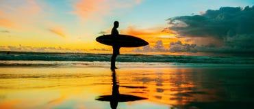 Persona que practica surf con el tablero Foto de archivo libre de regalías