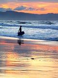 Persona que practica surf con el tablero de la boogie en la puesta del sol Fotografía de archivo libre de regalías