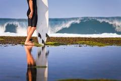 Persona que practica surf con la tabla hawaiana en una costa costa Fotos de archivo libres de regalías