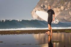 Persona que practica surf con la tabla hawaiana en una costa costa Fotos de archivo