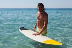 Persona que practica surf con la tabla hawaiana que se coloca en el mar Imagenes de archivo