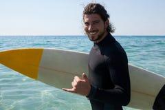 Persona que practica surf con la tabla hawaiana que se coloca en la costa de la playa Foto de archivo libre de regalías