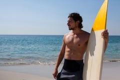 Persona que practica surf con la tabla hawaiana que se coloca en la costa de la playa Imágenes de archivo libres de regalías