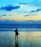 Persona que practica surf que corre en el océano Imagen de archivo libre de regalías