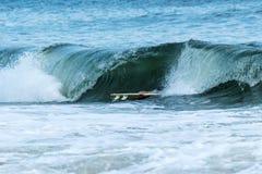 Persona que practica surf que cuelga encendido a su tabla hawaiana mientras que la onda se estrella encima Imagen de archivo libre de regalías