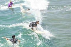 Persona que practica surf de deslizamiento entre otros que espera ondas Fotografía de archivo