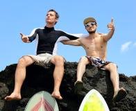 Persona que practica surf de dos amigos que se sienta en una roca Fotografía de archivo libre de regalías