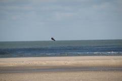 Persona que practica surf de la cometa del vuelo en la playa abandonada Imagenes de archivo