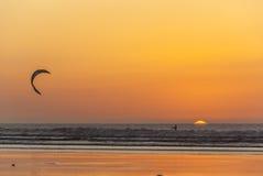 Persona que practica surf de la cometa en la puesta del sol Imagen de archivo libre de regalías