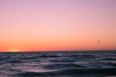 Persona que practica surf de la cometa en la puesta del sol Fotos de archivo libres de regalías