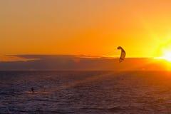Persona que practica surf de la cometa en puesta del sol Imágenes de archivo libres de regalías