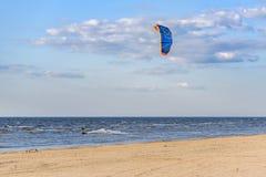 Persona que practica surf de la cometa que hace la línea de la costa de mar Báltico del nea de los trucos en Riga, Letonia Imagen de archivo libre de regalías