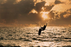 Persona que practica surf de la cometa que salta del agua Foto de archivo