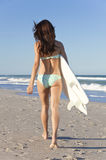Persona que practica surf de la mujer en bikiní con la tabla hawaiana en la playa Imagen de archivo