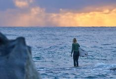 Persona que practica surf de la mujer joven que mira hacia fuera al mar imagen de archivo libre de regalías