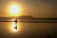Persona que practica surf de la puesta del sol Imagen de archivo