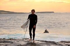 Persona que practica surf de la salida del sol en el cabo Solander Australia Fotografía de archivo