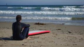 Persona que practica surf de sexo femenino que comtempla ondas imagen de archivo libre de regalías