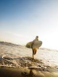 Persona que practica surf de sexo femenino con la tarjeta de resaca que recorre en la playa Imagenes de archivo