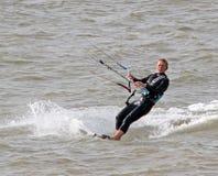 Persona que practica surf de sexo femenino de la cometa en el mar Imagenes de archivo