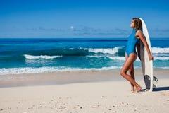 Persona que practica surf de sexo femenino en traje de baño azul con el tablero en manos en la costa costa Foto de archivo