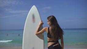 Persona que practica surf de sexo femenino hermosa que busca las ondas metrajes
