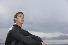 Persona que practica surf de sexo masculino pensativa que se sienta contra el cielo nublado en la playa Foto de archivo libre de regalías