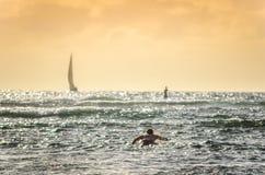 Persona que practica surf de sexo masculino que se bate hacia fuera en la puesta del sol en Hawaii con los veleros en fondo imágenes de archivo libres de regalías