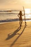 Persona que practica surf del bikiní de la mujer y playa de la puesta del sol de la tabla hawaiana Fotografía de archivo