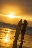 Persona que practica surf del bikiní de la mujer y playa de la puesta del sol de la tabla hawaiana Foto de archivo libre de regalías