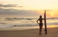 Persona que practica surf del bikiní de la mujer y playa de la puesta del sol de la tabla hawaiana Foto de archivo