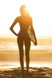 Persona que practica surf del bikiní de la mujer y playa de la puesta del sol de la tabla hawaiana Imágenes de archivo libres de regalías