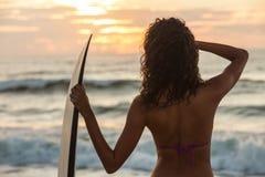 Persona que practica surf del bikin? de la mujer y playa de la puesta del sol de la tabla hawaiana foto de archivo libre de regalías